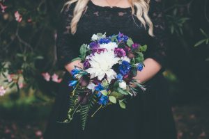Blue and purple bouquet on black wedding dress