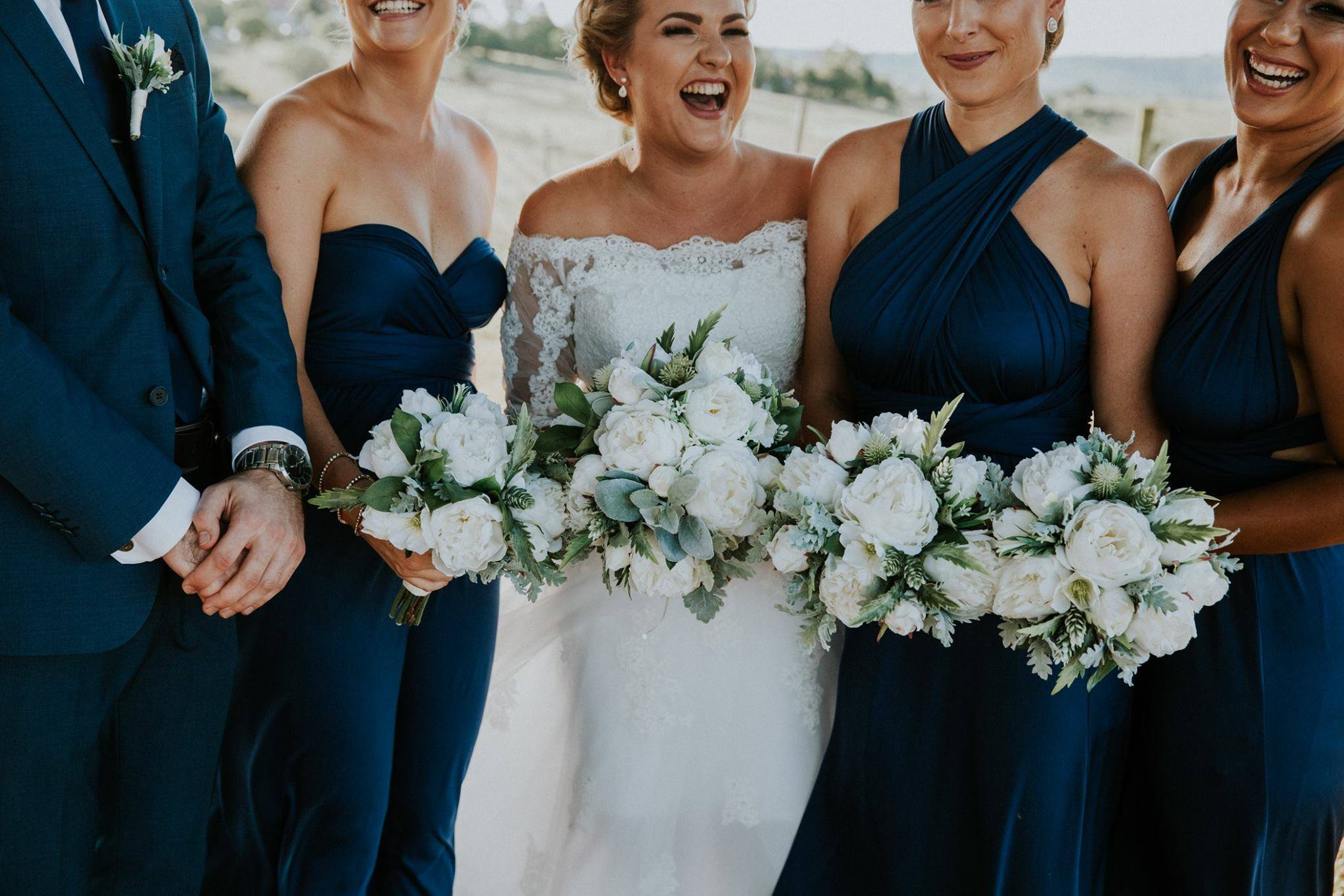 White and green bouquets on navy maids – image by Laura Slade Photography
