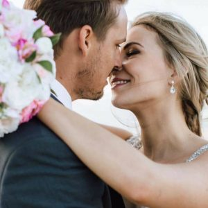 groom kissing bride with pink bouquet