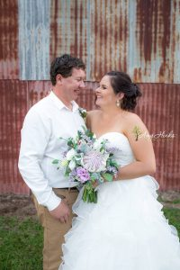 bride and groom with rustic flowers on tin shed