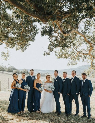 Peony bouquets on navy bridesmaids – image by Laura Slade photography