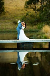 bride and groom on jetty on lake